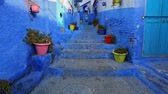 maroc : Traditional old blue street with color pots inside Medina of Chefchaouen, Morocco Stock Footage
