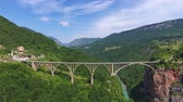 Aerial view on Djurdjevica arch bridge over the river in northern Montenegro, 4k