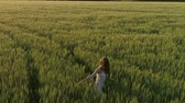 Beautiful girl walking in the wheat field at sunset, flying around