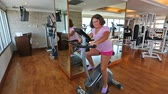 obezita : Overweight girl exercising on a cross-trainer machine in gym
