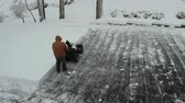clareira : This scene is a timelapse of a man clearing the top of his driveway. Though the man is dressed in a brown coat, there isnt much other color in the scene. He clears the snow in straight lines and only stops for a car that moves around the driveway for a fe