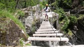 alpinista : Man walking wooden bridge on Via ferrata