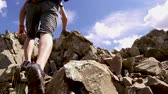 Man climbing rock while hiking on summer day in nature - Slow motion video