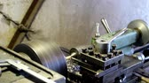 A plastic part is made on the lathe, the cutter moves slowly along the part and the shavings. Stock mozgókép