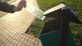 ebilmek : womens hand throws an empty plastic bottle into the trash can