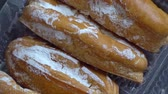 choux : Fresh eclairs sprinkled with powder rotate on the table