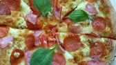 salame : close up. Pizza with tomatoes and cheese background rotating on the kitchen table