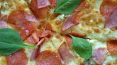 fesleğen : close up. Pizza with tomatoes and cheese background rotating on the kitchen table