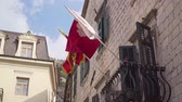 história : Kotor, Montenegro. Flag of Kotor and Montenegro on the facade of the old building Vídeos