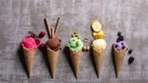 lody : variety of homemade ice-cream scoops in waffle cones on a grey background, stop motion animation Wideo