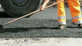 asphalt : Road construction worker leveling asphalt using rake while in the back road roller passing by