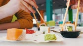 сакэ : Girl and a guy are sitting in a sushi bar and take with wooden sushi sticks
