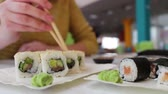 сакэ : Girl sits Takes with the wooden sticks a green wasabi in the cafe on the table are sushi, Japanese cuisine