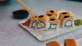 сакэ : Delicious sushi with salmon, cheese, wasabi, pink ginger, soy sauce Which are taken with wooden sticks on a stylish white wooden background Стоковые видеозаписи
