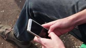 cellular : Young man Playing on mobile phone, looking at screen Stock Footage