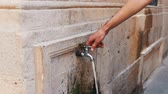 lack of water : The man opens the tap in a wall. Fountain for drinking in the city of Bacu street Stock Footage
