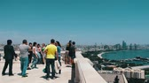 trees : MAY 9,2017 - AZERBAIJAN, BAKU: Tourists walk and take pictures at the observation deck with a view of a Caspian Sea and the Baku embankment