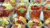 význam : Fresh freshly packed in a plastic glass mix of fruits of watermelon, kiwi, pear, apple, mango, pomegranate, strawberry in which the forks are stuck close up Dostupné videozáznamy