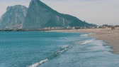 Мауи : Mediterranean Sea in its beautiful waves, beating against white sand and the Rock of Gibraltar against background