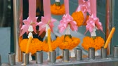 özveri : Wax candles and flowers near traditional Buddhist altar in Thailand Stok Video