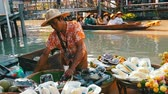 heyecan verici : PATTAYA, THAILAND - December 18, 2017: Seller in a colorful shirt and a straw hat sells exotic Thai fruits on a boat