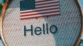 вывеска : Beautiful sign with American flag with the inscription Hello in English. Sign with the inscription Hello on background of palm trees in hot Thailand