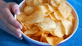 fattening : Woman is lying on a sofa under a blue blanket and is eating chips