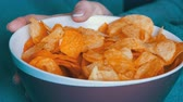fattening : Large plate with potato chips. The woman lies on the couch and eating potato chips, close up view Stock Footage