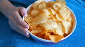 potato dishes : Beautiful well-groomed womens hands with French manicure eat potato chips from a huge plate on the couch Stock Footage