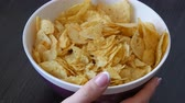 graxa : Large plate with potato chips on the table. Female hands with beautiful manicure take chips