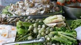 vietnamita : Various greenery that grows in Thailand. Boiled eggs on the counter. Counter with variety of Thai food. Asian street food