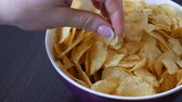 leading : Large plate with potato chips on the table. Female hands with beautiful manicure take chips
