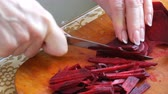 preparation clip : Female hands cut the beetroot on a kitchen board with knife Stock Footage