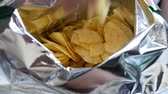 fornada : Teenager boy eats potato chips from a package. Unhealthy food, fast food
