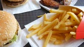 batatas fritas : On tray is fast food. Not healthy food on the table burgers, french fries and fried chicken wings