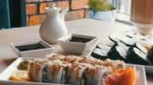 soja : Two sets of sushi rolls in a stylish, beautifully decorated cafe. Restaurant Japanese cuisine on the table next to sushi porcelain teapot for soy sauce and saucer