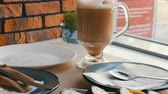 сакэ : Coffee latte in a clear glass cup next to sushi rolls in stylish cafe Стоковые видеозаписи