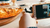 főétel : Teenager boy takes a photo of food on a smartphone. Japanese sushi rolls and Italian pizza on the restaurant table Stock mozgókép