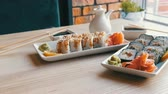 сакэ : Two sets of sushi rolls in a stylish, beautifully decorated cafe. Restaurant Japanese cuisine on the table next to sushi porcelain teapot for soy sauce and saucer