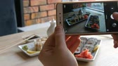 soja : Hands of a teenager make a photo of food on a smartphone. A set of sushi rolls from Japanese cuisine on the background of porcelain teapot for soy sauce and saucer in a stylish cafe Vídeos
