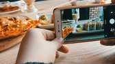 dish photo : Hands of a teenager make a photo of food on a smartphone. A set of sushi rolls from Japanese cuisine and pizza on the background of porcelain teapot for soy sauce and saucer in a stylish cafe