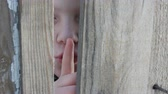 pokukování : Frightened teenager boy peeks through a gap between a fence or a doorway and shows a finger of a sign of silence, applying his index finger to his lips