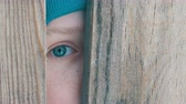 wintertime : Frightened eye of a teenage boy peeks into the door slot or crevice in the fence