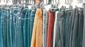 racks : Pants hang on hanger, women look at clothes and choose. Flea market, clothes sold on the market