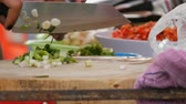 soja : Woman cuts greens on a kitchen board with a large knife. Next to vegetables and cooking utensils. Thai street food