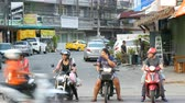 közlekedési mód : PATTAYA, THAILAND - DECEMBER 16, 2017: Girls and men on motobikes wait their turn to turn into traffic. Huge traffic on the streets of Thailand. A lot of cars, minibuses, motorcycles drive in a typical large Asian street Stock mozgókép
