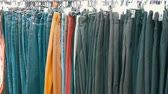 zábradlí : Pants hang on hanger, women look at clothes and choose. Flea market, clothes sold on the market