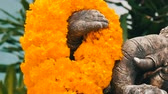 sembolizm : Statue of elephant in flowers close up view. Elephant symbol of Thailand. Buddhist religion and symbols Stok Video