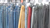 butik : Pants hang on hanger, women look at clothes and choose. Flea market, clothes sold on the market