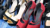 garaj : PATTAYA, THAILAND - DECEMBER 16, 2017: Flea market in Thailand. People choose things on a flea market. Many second-hand things on the floor. A lot of toed shoes with heels and different colors Stok Video